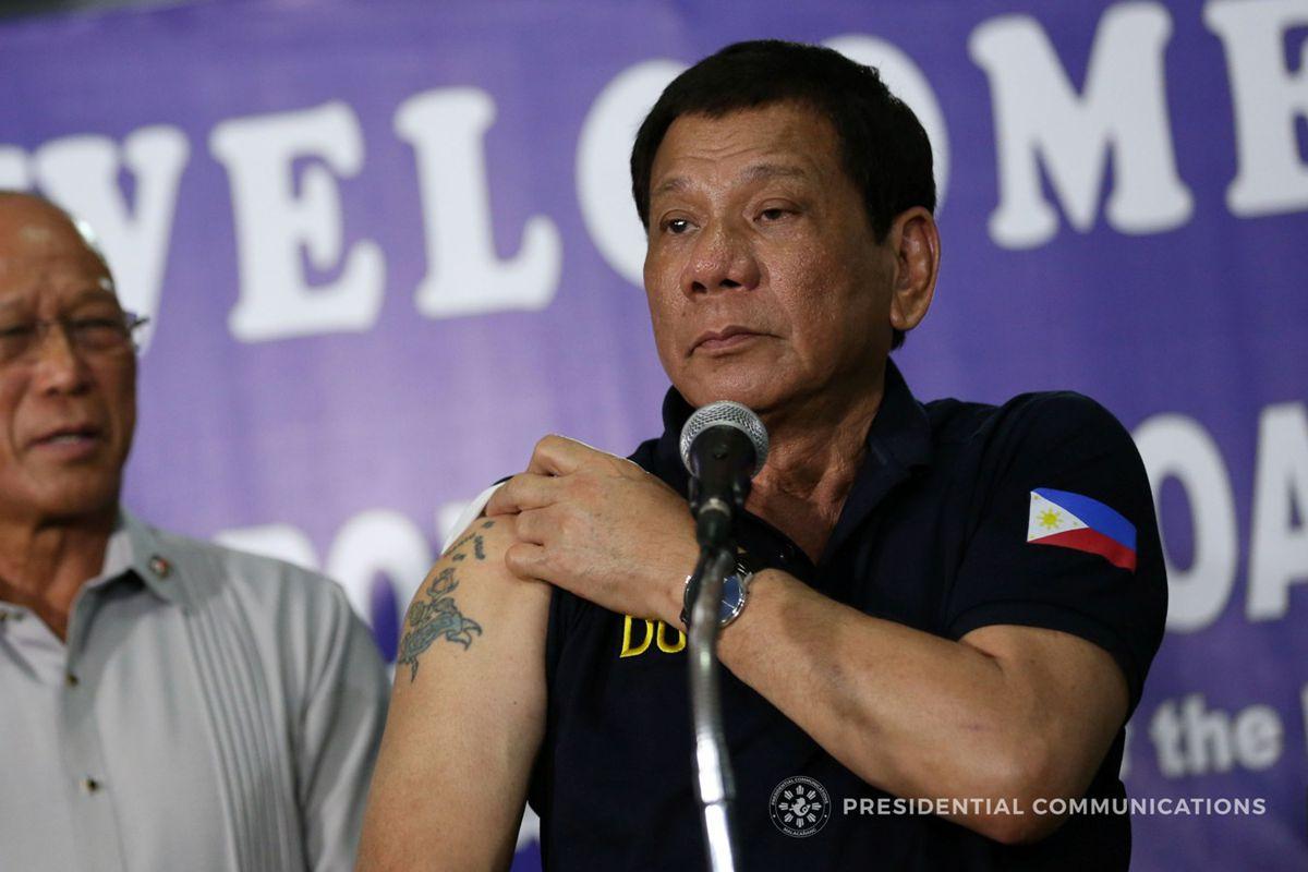 Родриго Дутерте (президент Филиппин) демонстрирует свою татуировку перед журналистами