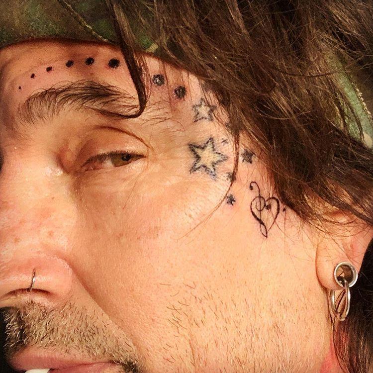 татуировка звездочки скрипичный и басовый ключ на лице Томми Ли